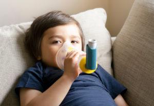 criança deitada em um sofá segurando uma bombinha de tratamento de crise de asma