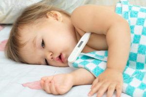 Bebê deitado com aparência de febre com termômetro embaixo do braço e coberto com manta quadriculada azul claro e branca